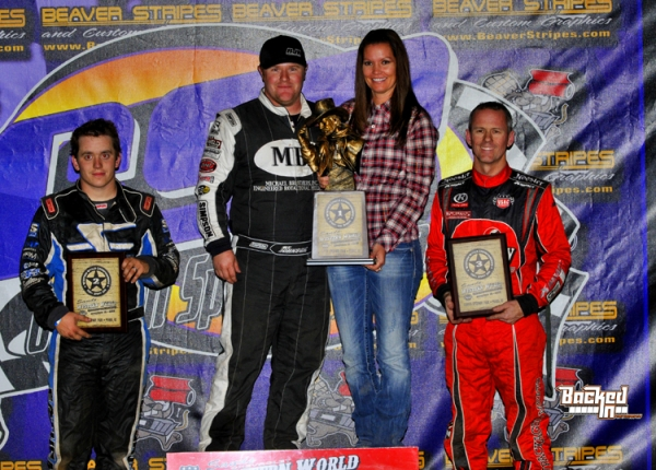 "R.J. Johnson stands atop the ""Western World"" Sprint podium Thursday. Brady Bacon took second and Jerry Coons Jr. third."