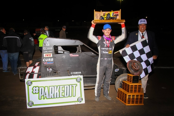"2016 ""Turkey Night Grand Prix"" winner Kyle Larson hoists the trophy in victory lane next to J.C. Agajanian, Jr. Thursday night at California's Ventura Raceway."
