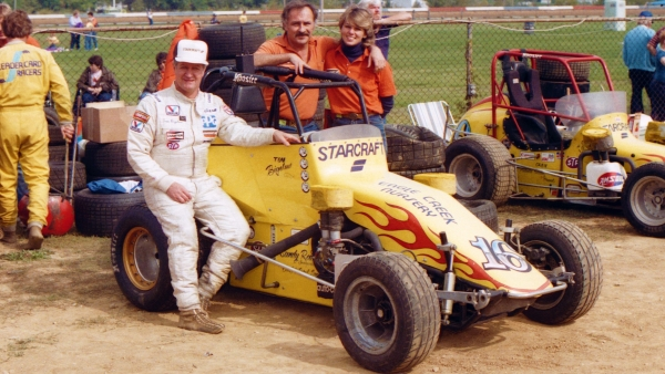 Carl Sandy (Middle) with driver Tom Bigelow, sitting on right rear tire, during Bigelow's 1984 USAC National Midget driving title season.